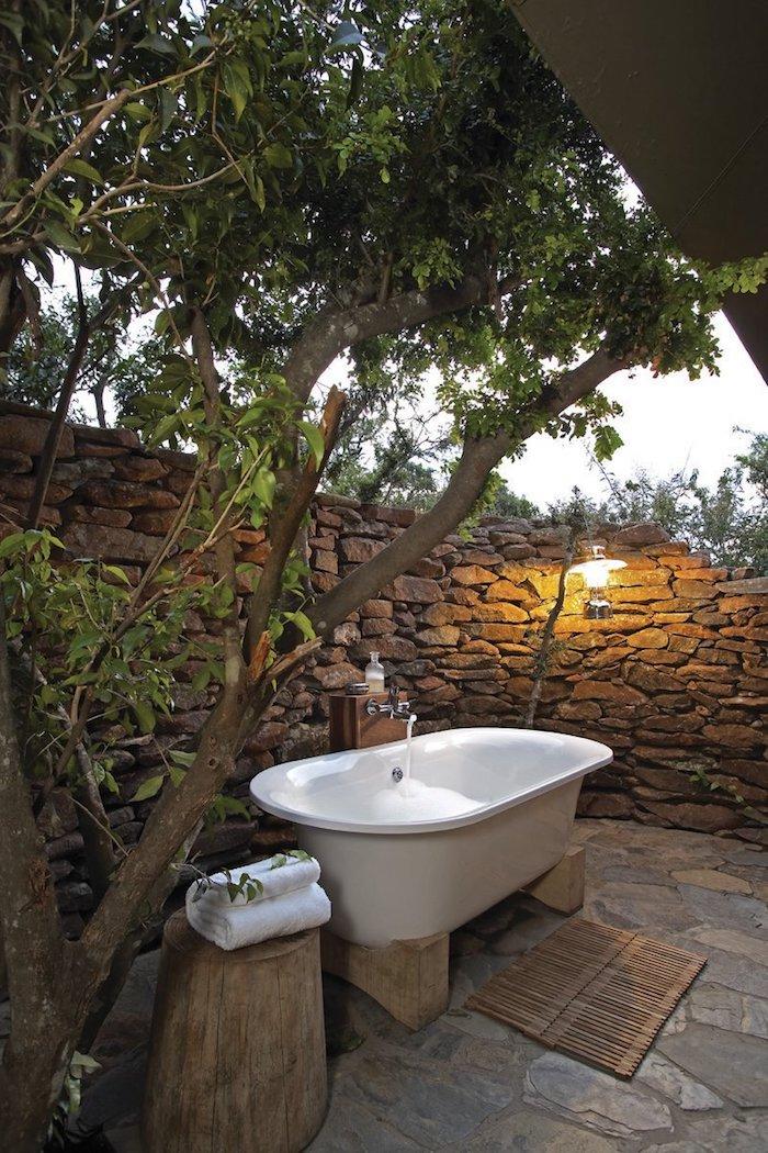 ein weißes kleines tuch und weiße badewanne im garten mit einem zaun sichtschutz aus grauen steinen, sichtschutz für gartendusche selber bauen