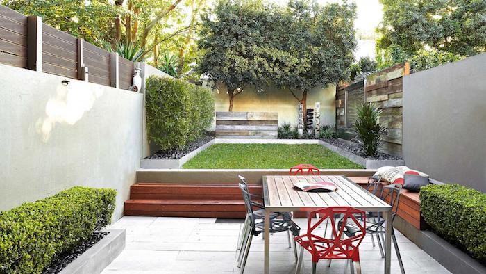 grüne hecke und ein tisch im garten mit einem zaun sichtschutz aus holz und mit einem grünen rasen, bäume mit grünen blättern, gartengestaltung ideen diy