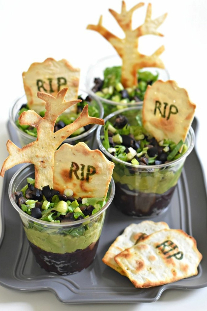 Halloween Snack Ideen, kleine Crackers und Becher mit grünen und braunen Süßigkeiten, wie Friedhof