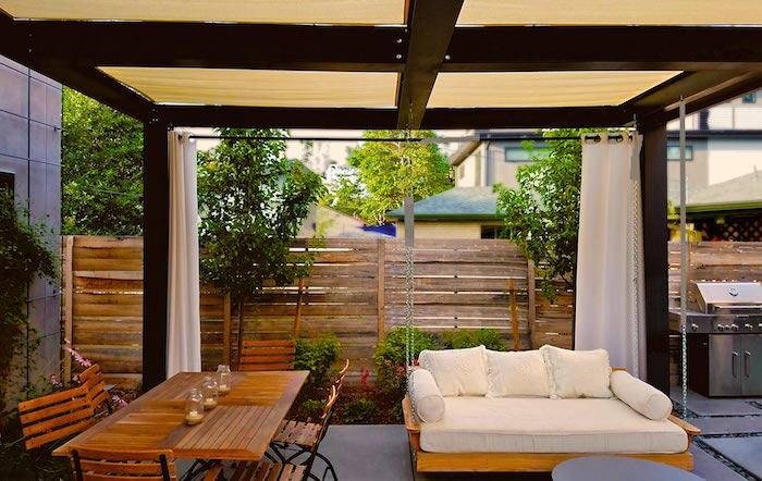 sofa mit weißen kissen und brauner tisch aus holz im garten mit überdachung mit weißen vorhängern, ein zaun aus holz als sichtschutz
