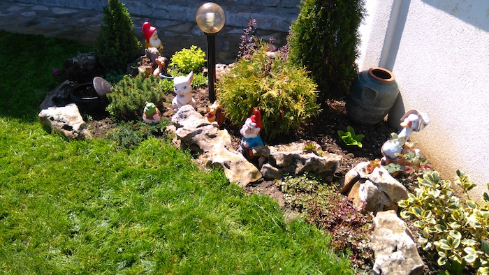 grüner rasen und kleiner sreingarten mit steingartendeko mit einem weißen hase und roten zwergen und steinen für steingarten