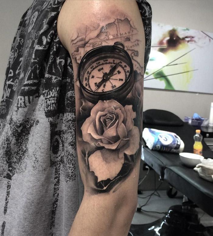 tattoo 3d am oberarm, weiße rose in kombination mit weltkarte und kompass, mann