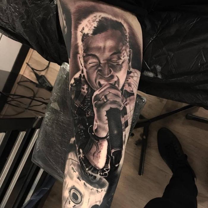 tattoo bilder arm, realitische tätowierung am oberarm, chester, mann mit mikrofon