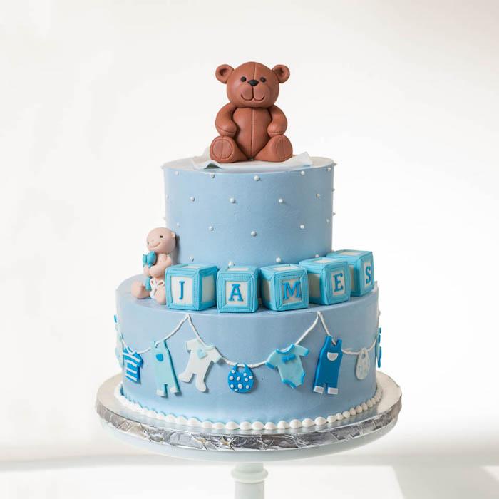Zweistöckige Tauftorte für Jungen mit süßen Figuren aus Fondant, Bär und Würfel mit dem Namen des Babys