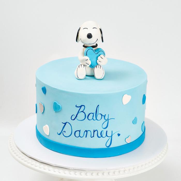 Blaue Tauftorte mit dem Namen des Babys und kleinen Herzen, süße Hund Figur aus Fondant