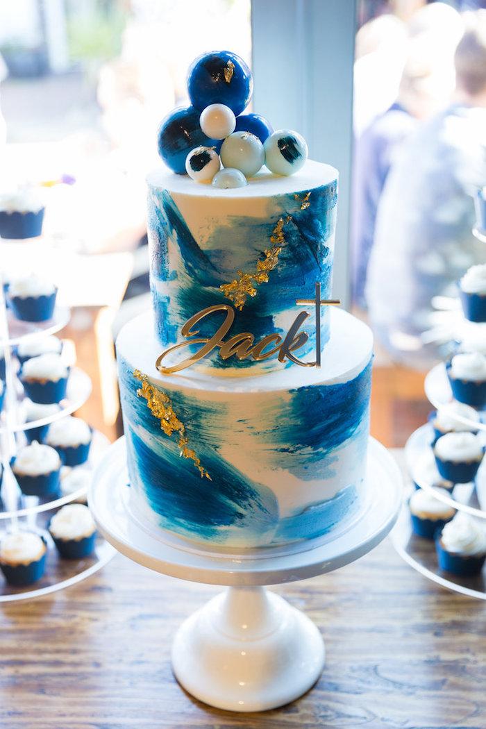 Zweistöckige Torte mit Bällen aus Fondant, goldene Aufschrift, Name des Babys und Kreuz