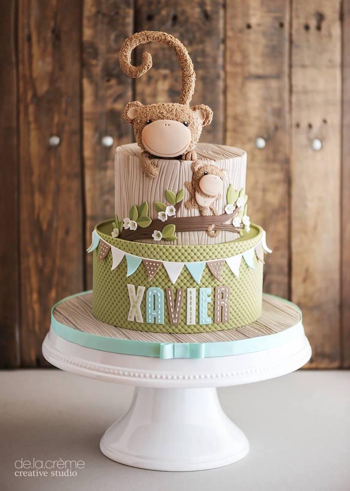 Zweistöckige Torte zur Taufe mit zwei Affen, Name des Babys, in Grün und Braun, auf Tortenständer