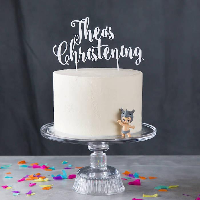 Idee für Torte zur Taufe mit weißer Creme, weiße Aufschrift und Plastikfigur Baby