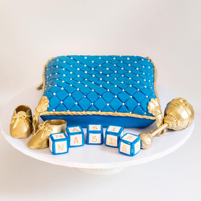 Fondant Torte zur Taufe in Form von Kissen, goldene Babyschuhe und Würfel mit dem Namen des Babys