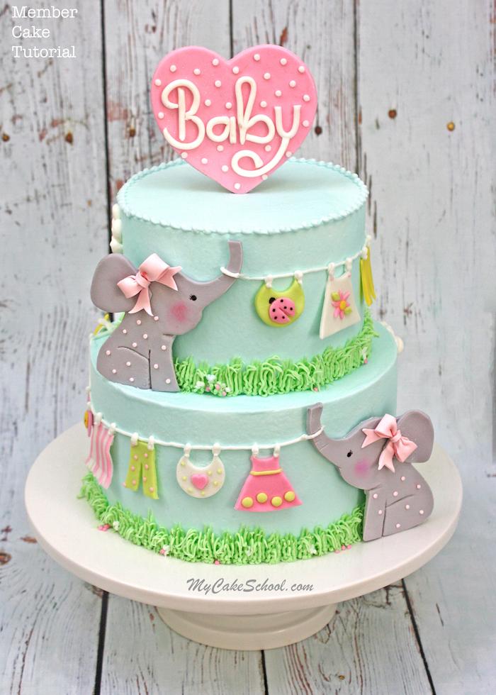 Zweistöckige Torte mit süßen Figuren aus Fondant, Babykleider und zwei Elefanten, Herz mit Aufschrift Baby