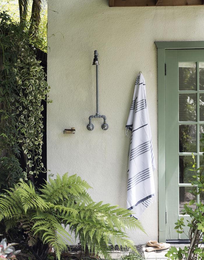 haus mit einem grünen fenster, eine weiße wand mit gartendusche edelstahl, sichtschutz aus grünen pflanzen und ein weißes tuch