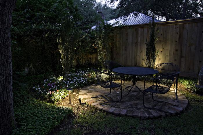 baum und ein schwarzer tisch und drei schwarze stühle, leuchten und kleine blumen und ein zaun aus holz und grüne kletterpflanzen als sichtschutz