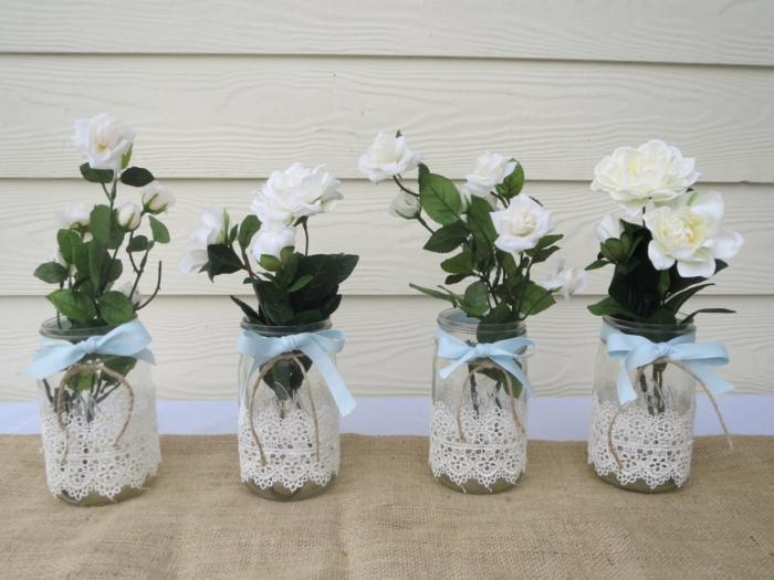 vier Vasen mit weißen Rosen, blaue Schleifen und Spitze darum, alles für die Hochzeit