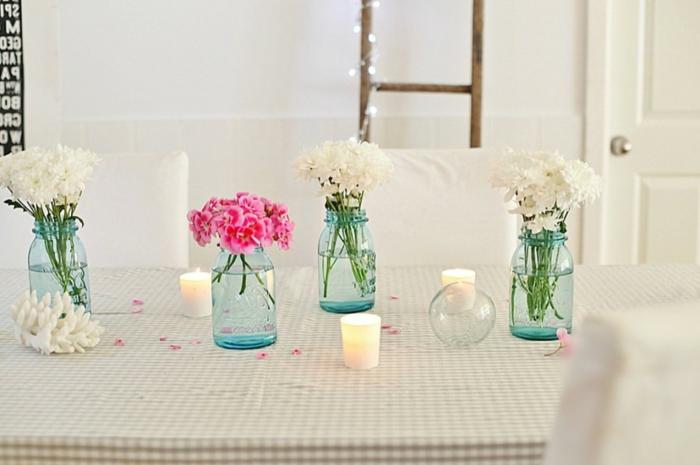 vier Vasen in blauer Farbe, drei voller weiße Blumen und eine voller rosa Blumen, Kerzen dazwischen, Deko für Hochzeit