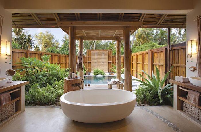 ein schwimmpool im garten mit vielen grünen flanzen und einer kleinen weißen badewanne und einer gartendusche mit sichtschutz aus holz