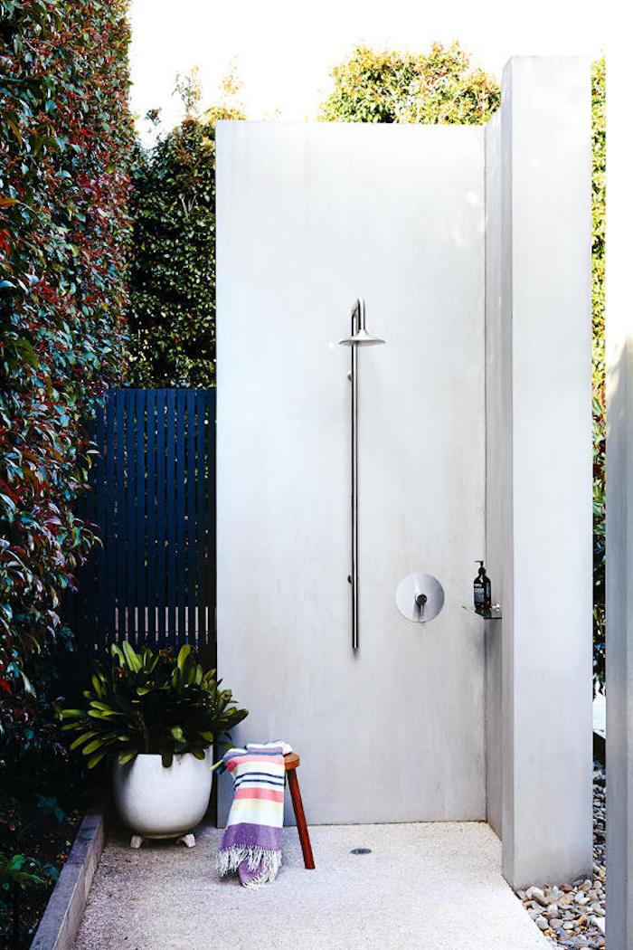 weißer sichtschutz für eine gartendusche, eine wand aus grünen kletterpflanzen , kleiner stuhl mit einem tuch