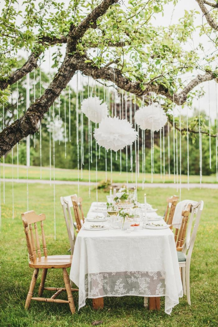 weiße Pompons, die über den Tisch hängen, alles für die Hochzeit, ein schöner Tisch