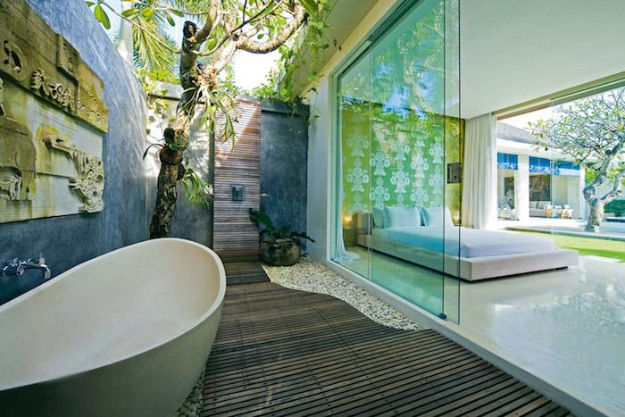 schlafzimmer mit einem weißen bett mit kleinen weißen kissen und eine terrasse mit einem braunen boden aus holz und mit einer kleinen weißen badewanne, ein baum mit grünen blättern und eine gartendusche