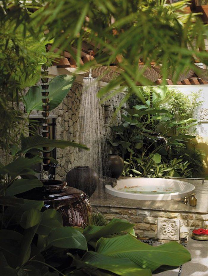 kleine gartendusche und eine we3iße badewanne mit einem sichtschutz aus vielen grünen pflanzen mit grünen blättern