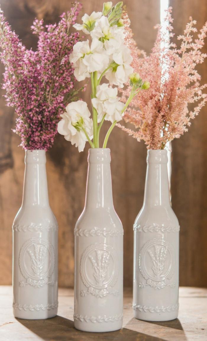Vasen aus Bierflaschen, mit weißen Farbe bedeckt, voller Frühlingsblumen, alles für die Hochzeit