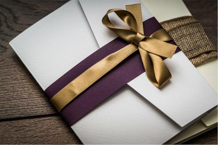 weißer Briefumschlag mit lila Band und einer goldenfarbenen Schleife gebunden, Hochzeitsdeko