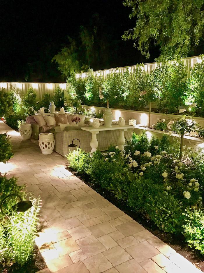 weißer gartenweg in einem garten mit grünen pflanzen und mit weißen blumen, sofas aus rattan und mit violetten und weißen kleinen kissen