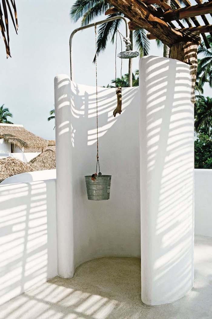 große palmen mit grünen blättern und ein garten mit einem weißen sichtschutz aus weißen wänden
