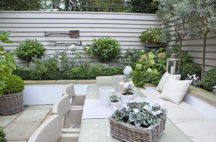 weißer zaun aus holz, sichtschutz sichtschutz mit hochbeeten mit grünen pflanzen mit grünen blättern, ein tisch und weiße stühle aus rattan, sofas mit kleinen weißen kissen