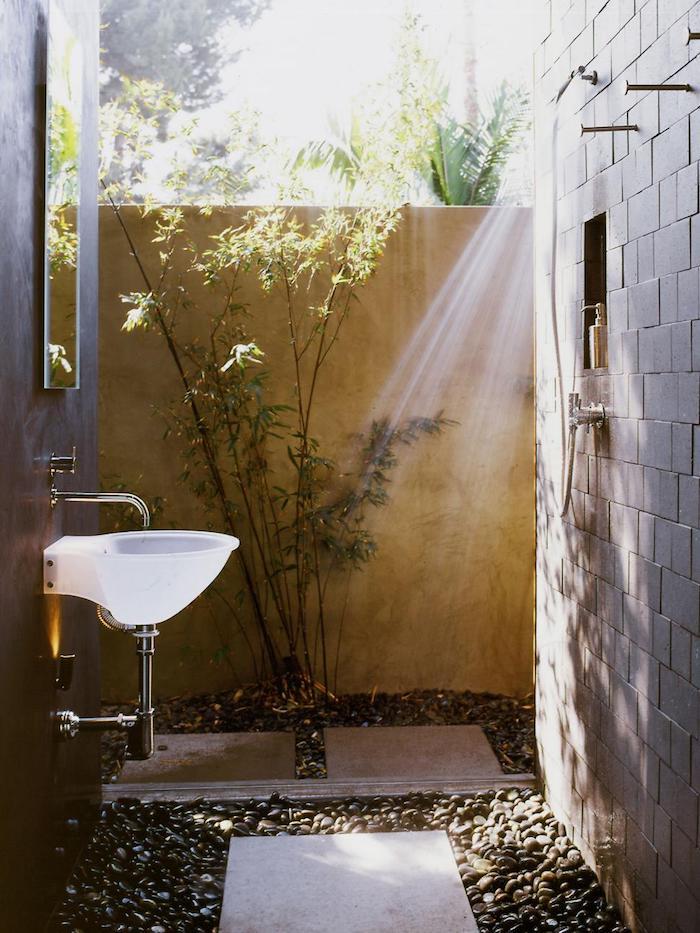 kleines weißes waschbecken im garten mit einem boden mit kleinen schwarzen steinen und mit einem spiegel, sichtschutz zaun