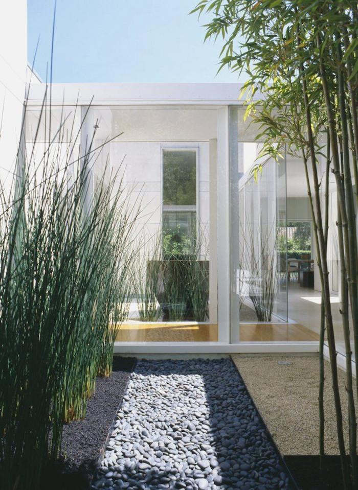 blauer himmel und ein haus mit weißen wänden und kleiner steingarten mit grauen kleinen steinen und mit grünen pflanzen und langen bambus stäben