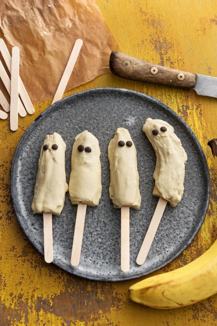 Bananen wie Gespenster, in weißer Creme getauft mit schwarzen Bonbons als Augen, Halloween Snack Ideen