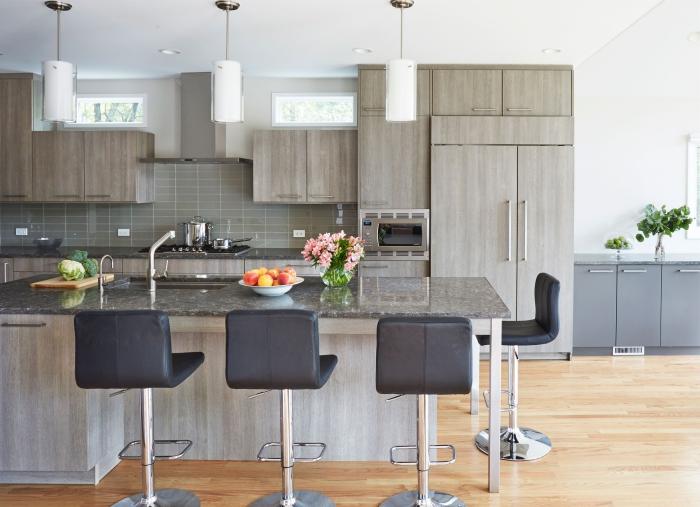 wohnungseinrichtung ideen, schwarze barstühle, große kücheninsel, glasvasen mit blumen