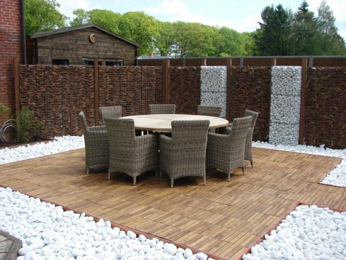 brauner boden aus holz und viele stühle aus rattan und ein tisch, gartenboden mit vielen weißen steinen und ein zaun aus gabionen mit weißen und braunen natursteinen