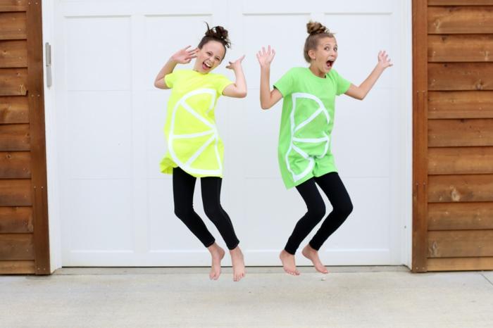 zwei Freundinnen, die springen mit grünen und gelben Blusen wie Zitrone und Limette, Halloween Verkleidung