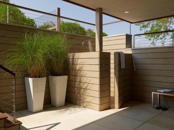 blauer himmel und ein haus mit einer terrasse mit gartendusche mit braunem sichtschutz aus holz und zwei große weiße blumentöpfe mit grünen pflanzen