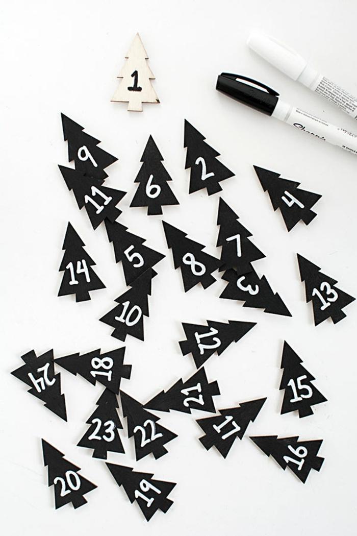 eine weiße Figur von Tannenbaum mit der Nummer Eins, die anderen Tannenbäume sind schwarz mit weißen Buchstaben, Adventskalender basteln