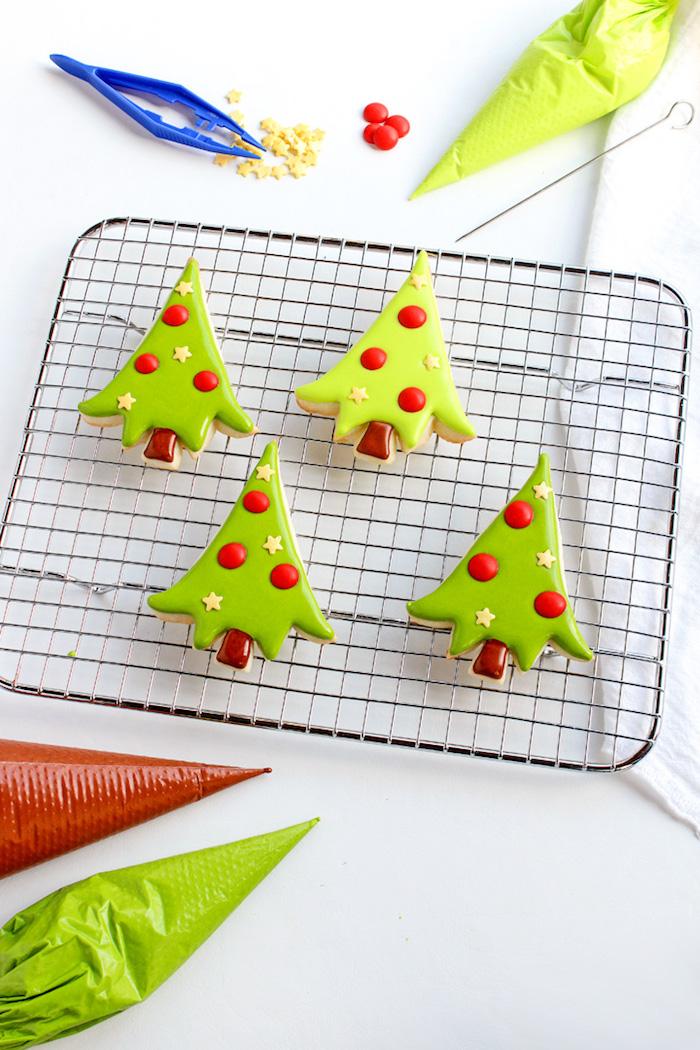 Weihnachtsplätzchen zum Ausstechen, kleine Christbäumchen mit roten Christbaumkugeln und gelben Sternchen