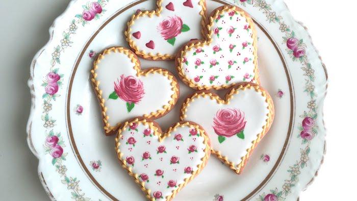 Plätzchen in Form von Herzen dekoriert mit Zuckerguss, Rosen mit Glasur malen