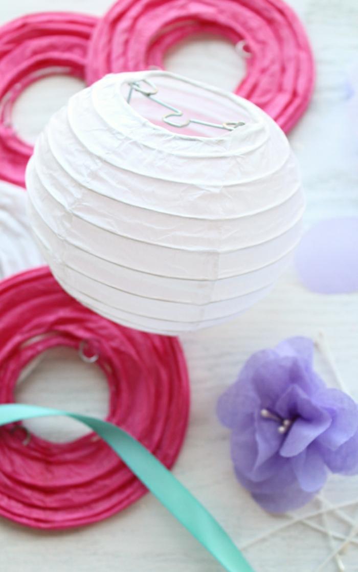 eine weiße Laterne und viele rosa Laternen, Bastelanleitung Laterne, lila Blume als Dekoration