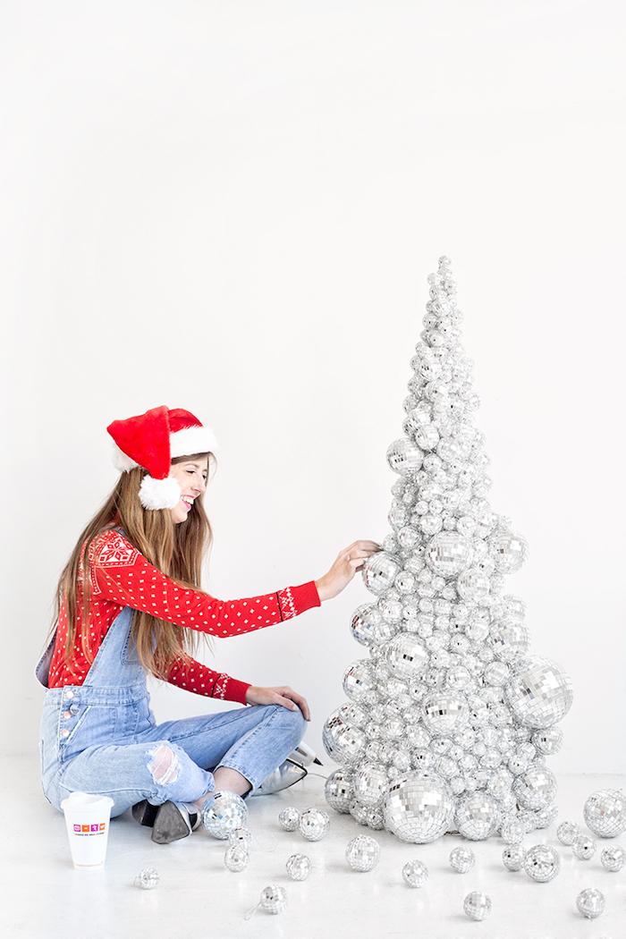 Kleine Diskobälle am Konus befestigen, silbernen Weihnachtsbaum selbst gestalten