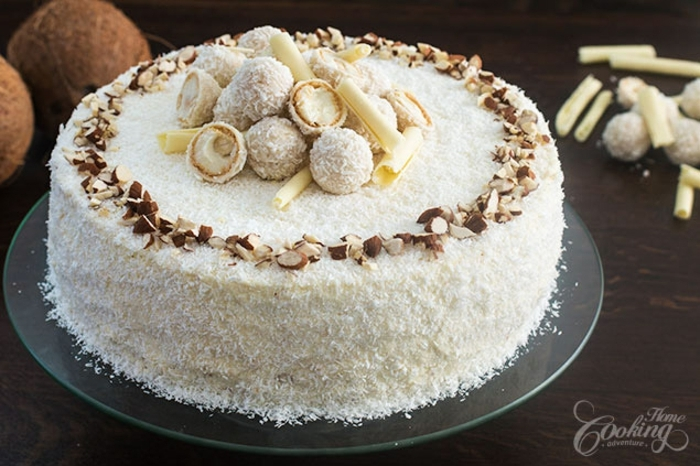 Raffaello Torte mit Pralinen geschmückt, mit zerkleinerte Mandeln umrandet, mit Kokosraspeln bedeckt