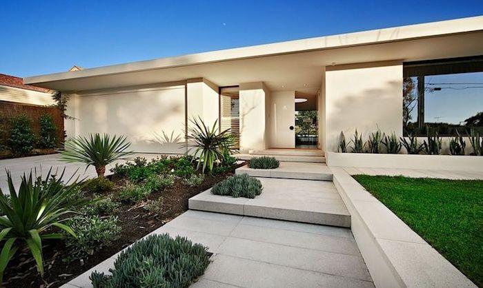 weißes haus mit einem kleinen vorgarten mit palmen und klenen grünen vorgarten pflanzen und einem grünen rasen