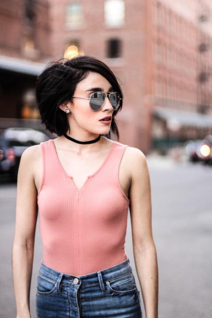 asymetrischer bob, rosarotes top mit jeans schwarze haarfarbe brille und choker accessoires, trendy look