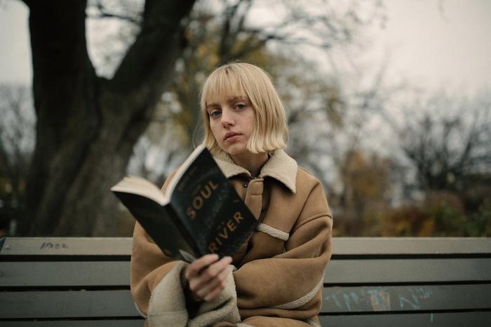 bob frisuren kurz blond, großer mantel eine frau sitzt auf bank und liest ein buch