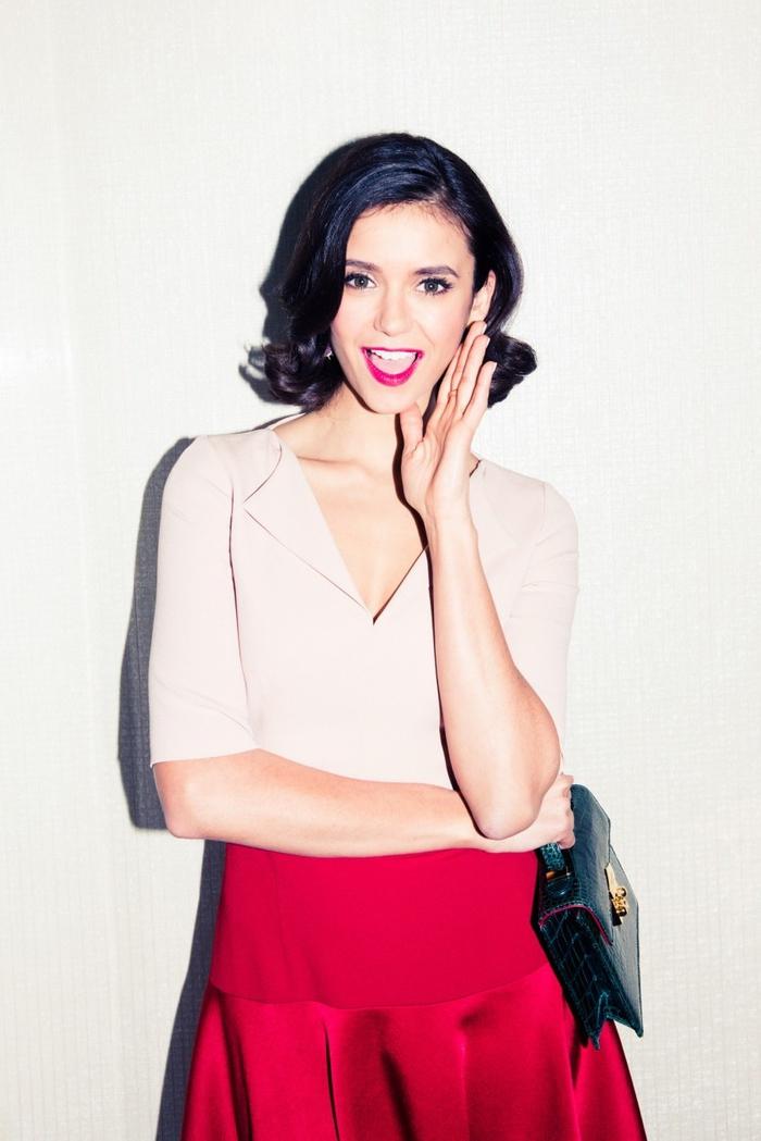 pagenschnitt frisur mit retro wellen, weiße bluse, roter rock, schöne tasche schwarz