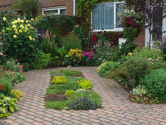 haus mit weißen fenstern und ein kleiner vorgarten mit grünen pflanzen und violetten und gelben blumen, einen vorgarten modern gestalten