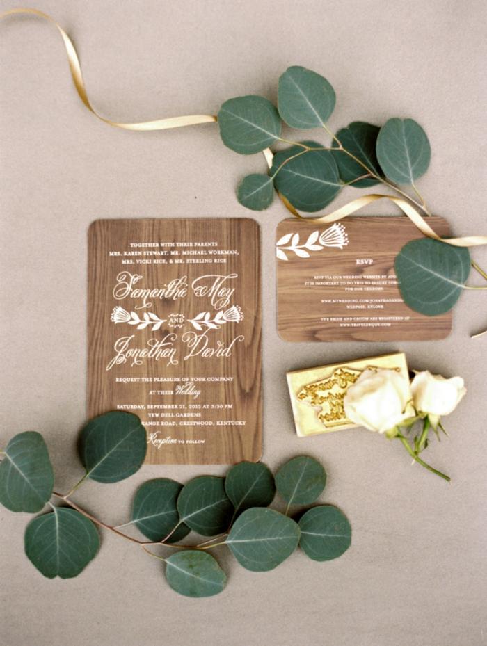 graviertes Holz als Einladungskarten, weiße Buchstaben und eine weiße Blume, Einladungskarten selber basteln