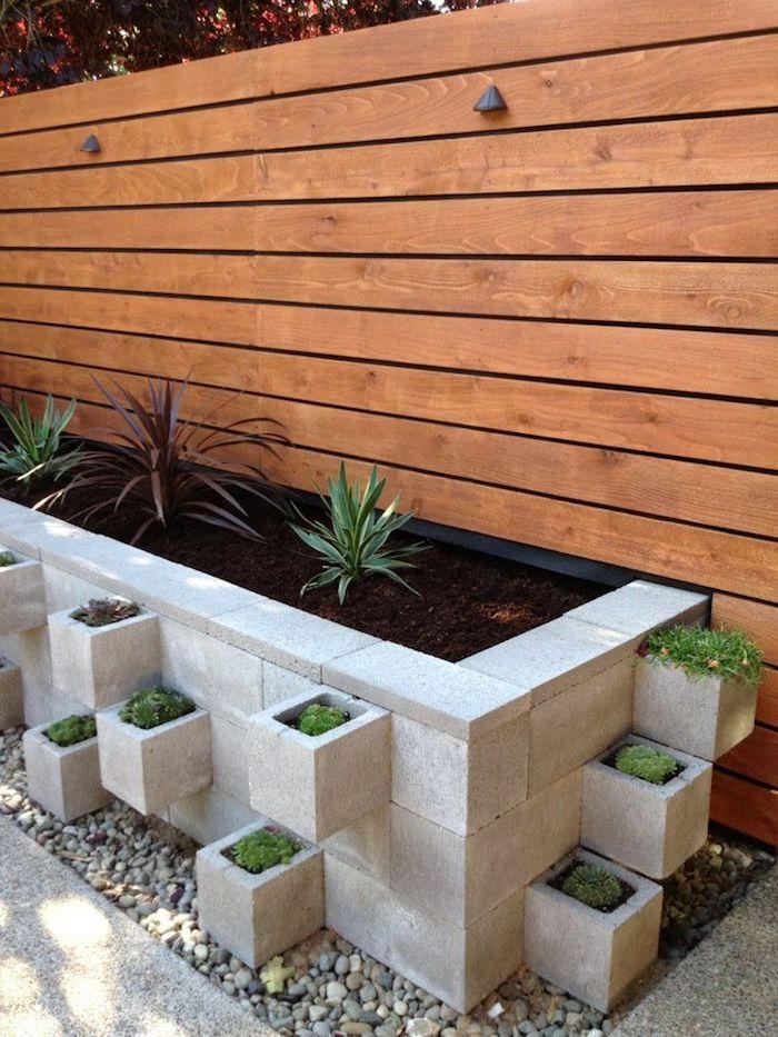 zaun aus holz und ein hochbeet mit grünen pflanzen mit grünen blättern und kleinen steinen, einen kleinen vorgarten modern gestalten, sichtschutz selber bauen