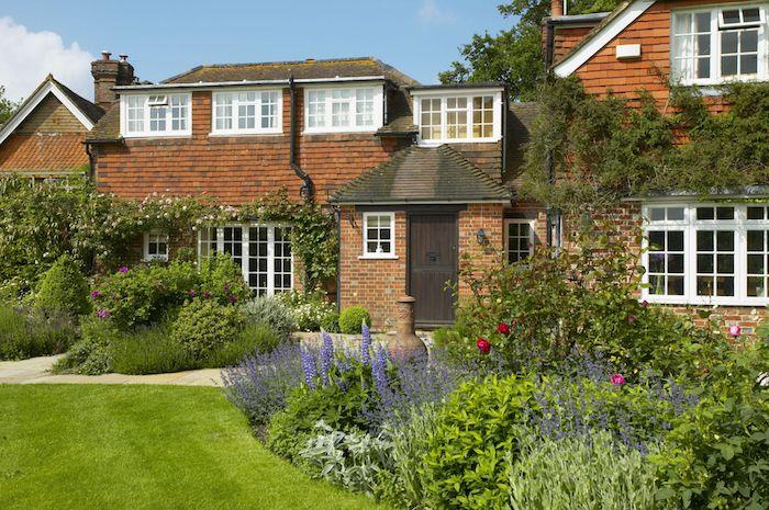 großes braunes haus mit weißen fenstern und ein vorgarten mit einem grünen rasen und violetten blumen und roten rosen und grünen blättern und kletterpflanzen