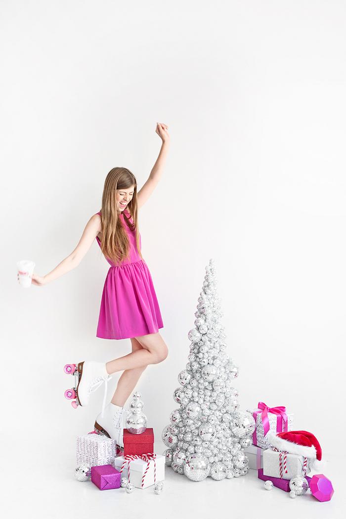 Silberner Weihnachtsbaum aus kleinen Diskobällen, Frau mit violettem Kleid und Rollschuhen, viele Weihnachtsgeschenke
